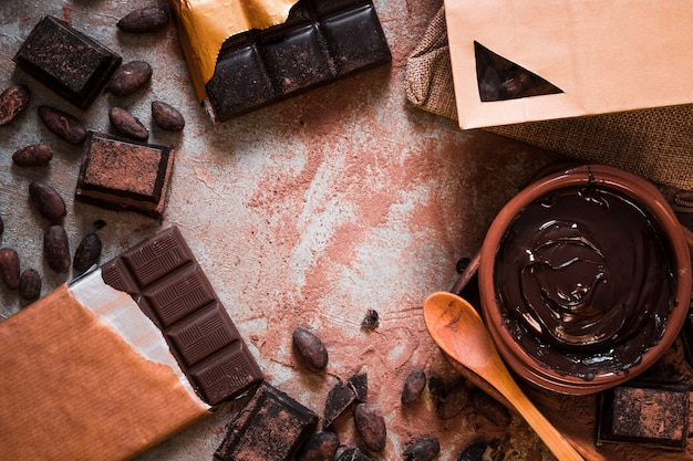 Chocolate bar, cocoa beans, and chocolate cream on table