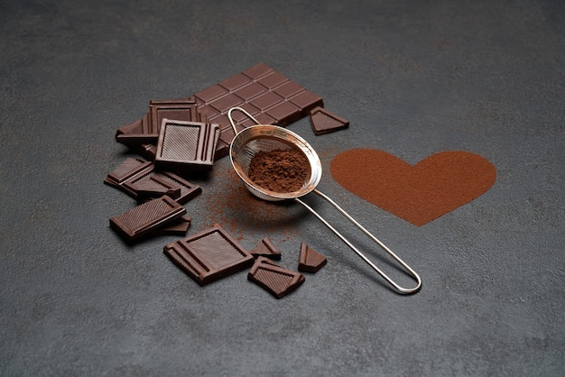 Chocolate bar and cocoa powder on dark concrete table