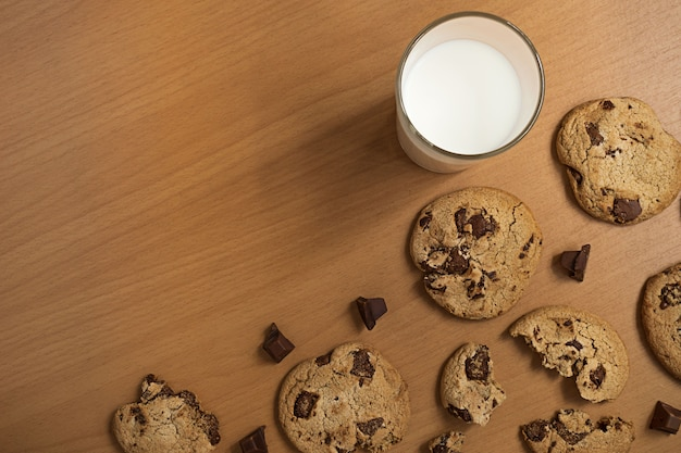 Chocolate bar and cookies and cup of milk, flat lay background