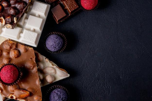 초콜릿 바, 으깬 다크 초콜릿과 견과류 조각. 프랄린 초콜릿 과자. 공간을 복사하십시오.