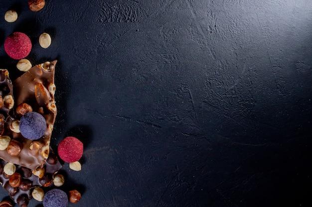 Плитка шоколада, измельченные кусочки темного шоколада и орехи. пралине шоколадные конфеты