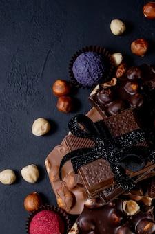 Плитка шоколада, измельченные кусочки темного шоколада и орехи. пралине шоколадные конфеты.