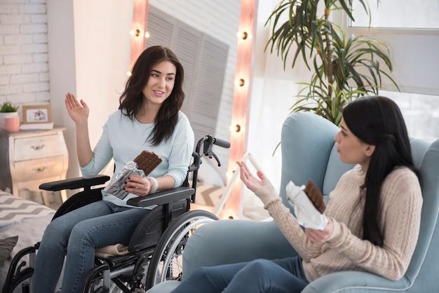 Плитка шоколада. радостная женщина-инвалид и подруга пробуют плитку шоколада и болтают