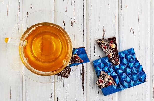 白い木製のテーブルの上にお茶を入れたアメジストの形のチョコレートバー。