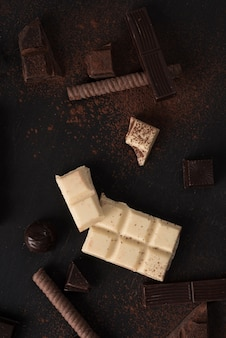 Chocolate bar pieces and candies over wooden surface