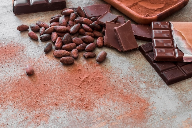 Chocolate bar pieces, cocoa beans and powder on wooden table