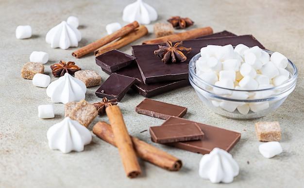 Кусочки шоколада, специи, коричневый сахар, безе и зефир. концепция фото сладкой еды.