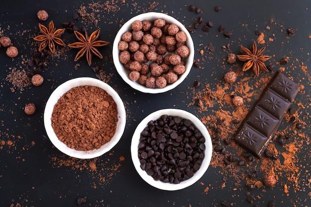 어두운 테이블 상단보기에 달콤한 음식을 요리하기위한 재료와 초콜릿 바 조각