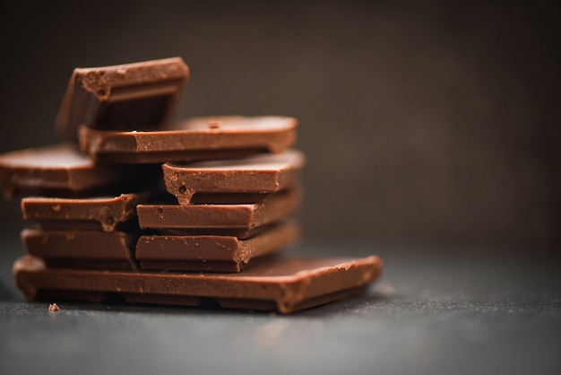 Chocolate bar stacked on the dark background chocolate pieces