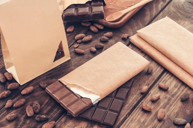Barretta di cioccolato con fave di cacao sulla tavola di legno