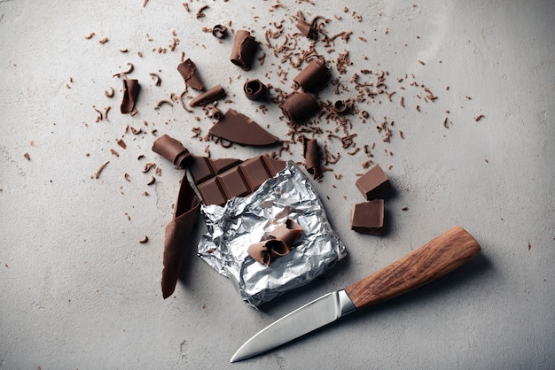 Chocolate bar with curls and knife on grey
