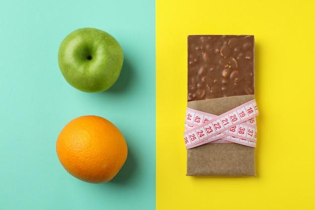 Плитка шоколада с рулеткой, яблоко и апельсин на двух тонах