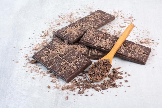 Шоколадный батончик с ложкой и какао на сером фоне. фото высокого качества