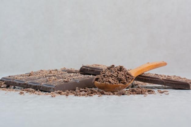 Barretta di cioccolato con cucchiaio e cacao su sfondo grigio. foto di alta qualità