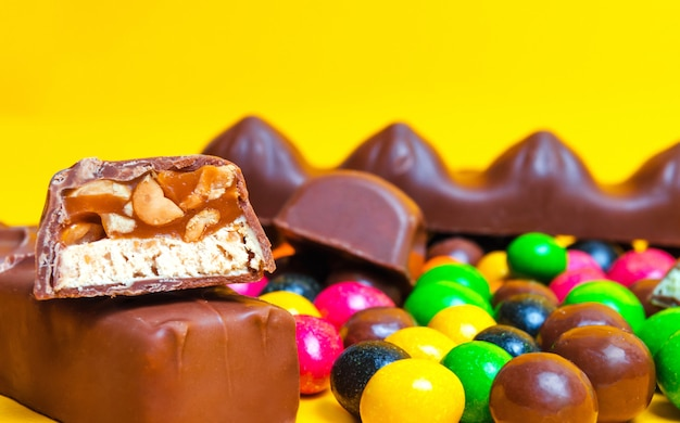 Chocolate bars, colorful candies, sweets on a yellow background. concept sweets