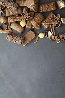 バックライトの黒い背景にチョコレートバー。詰め物入りチョコレート。おやつやお茶のお菓子。