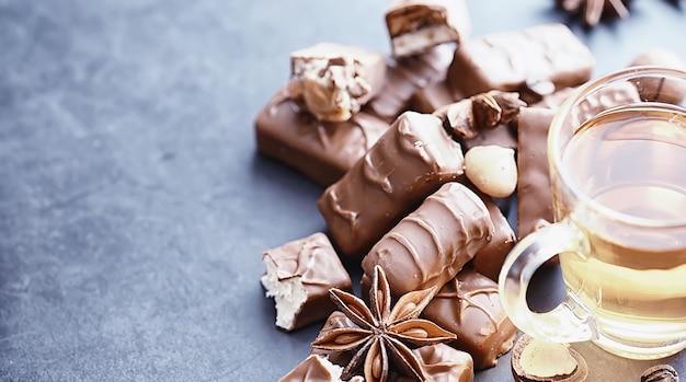 Шоколадные батончики на черном фоне с подсветкой. шоколад с начинкой. сладкие сладости к закускам и чаю.
