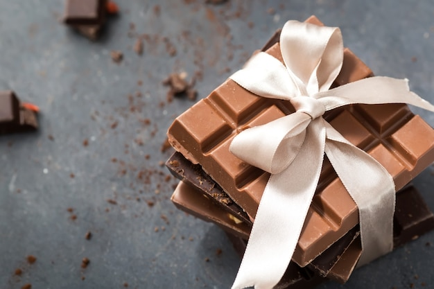 Chocolate bars with beige bow on a grey
