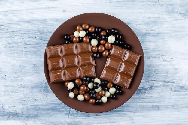 Шоколадные батончики с шоколадными конфетами в тарелке
