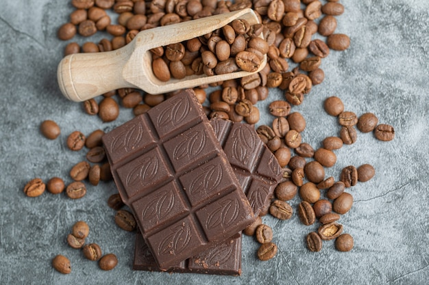 Chocolate bars with coffee beans on gray.