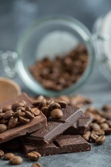 Barrette di cioccolato con chicchi di caffè su grigio.