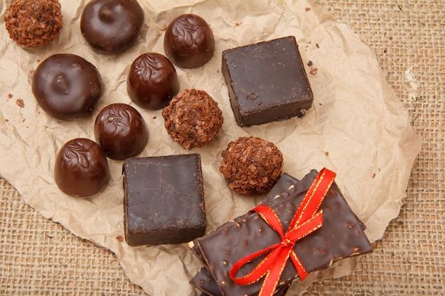 Плитки шоколада с орехами, конфеты из черного и молочного шоколада прямоугольной формы и в форме сердца на пачке. вид сверху.