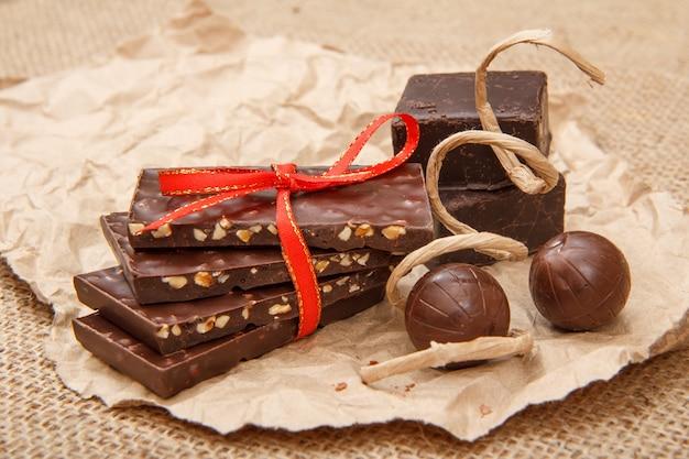 Плитки шоколада с орехами, перевязанные красной лентой, и шоколадные конфеты на листе упаковочной бумаги.