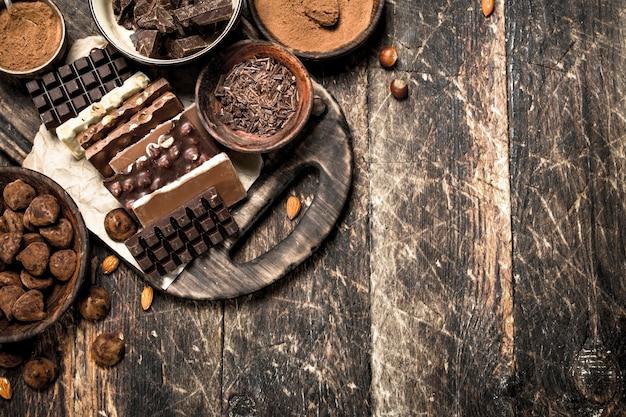 Плитки шоколада с трюфелями и какао-порошком на деревянном фоне