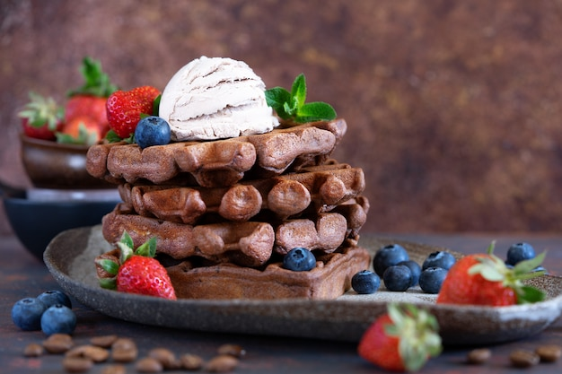 Chocolate belgian waffles with fresh berries and coffee ice cream on a ceramic plate on brown table