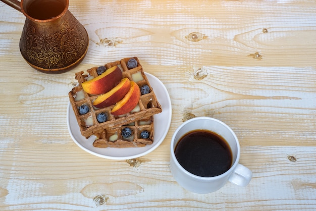 Chocolate belgian waffles with fruits, cup of coffee and cezve on white wooden table. delicious breakfast. top view