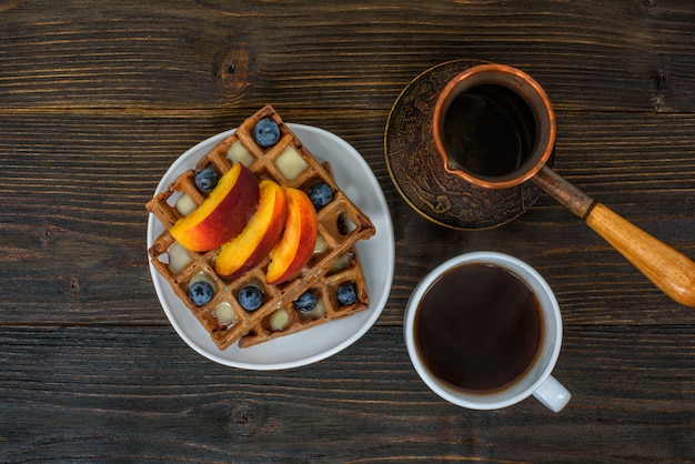 Chocolate belgian waffles with fruits, cup of coffee and cezve on wooden background