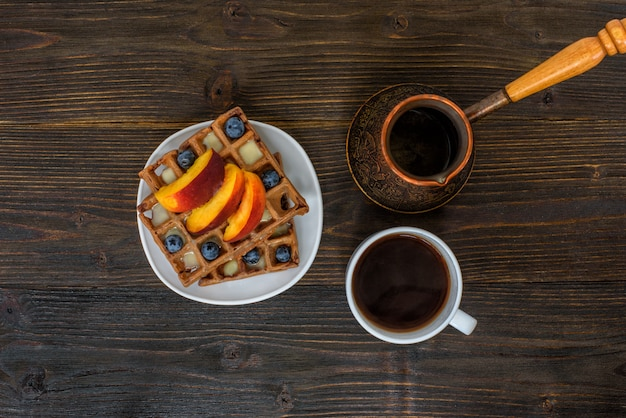 Chocolate belgian waffles with fruits, cup of coffee and cezve on wooden. delicious breakfast. top view
