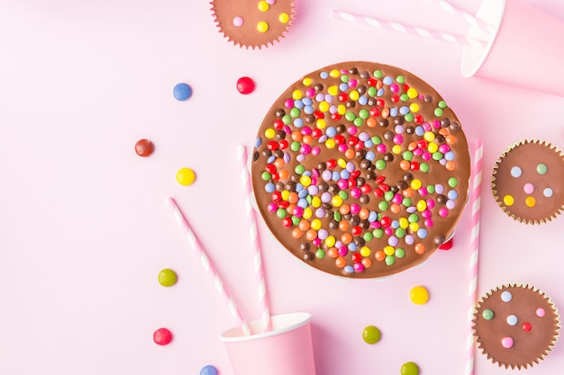 Chocolate birthday cake with multicolored candy sprinkles buttercups paper drinking cups