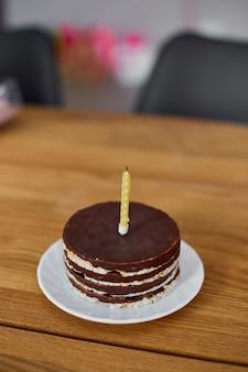 Шоколадный торт ко дню рождения с одной свечой на деревянном столе