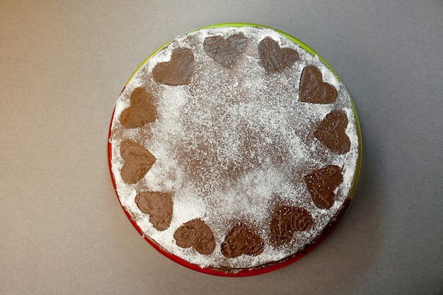 Chocolate biscuit cake with cocoa cream with small hearts from powdered sugar. dessert. valentine's day concept. flat lay top view