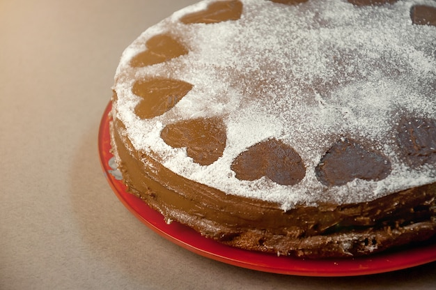 Chocolate biscuit cake with cocoa cream with small hearts from powdered sugar. dessert. valentine's day concept.