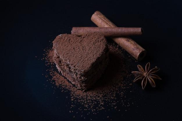 코코아 가루를 뿌린 심장 형태의 초콜릿 비스킷 capkake는 계피 옆에 어두운 배경에 놓여 있습니다.