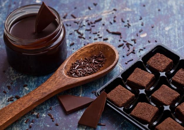 Шоколадный бисквитный песочный десерт на синей доске с банкой жидкого шоколада и деревянной ложкой