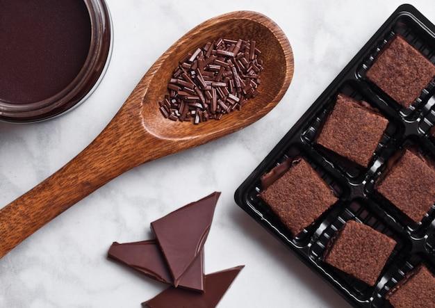 液体チョコレートと木のスプーンの瓶と大理石のボード上のチョコレートビスケットショートケーキデザート