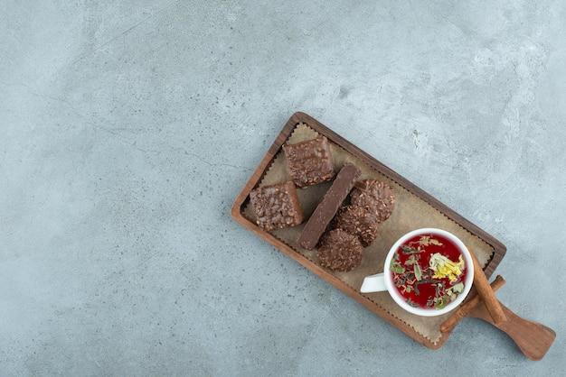 木の板にチョコレートビスケットとお茶。高品質の写真