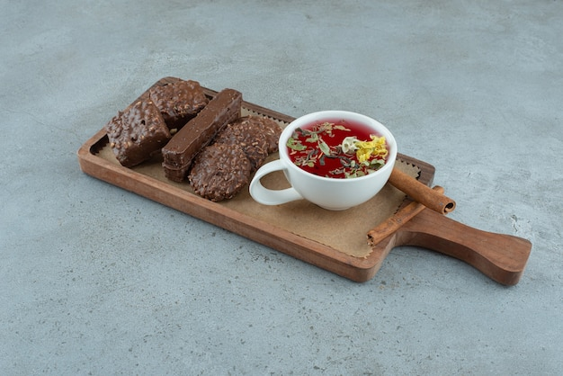 Шоколадное печенье и чашка чая на деревянной доске. фото высокого качества