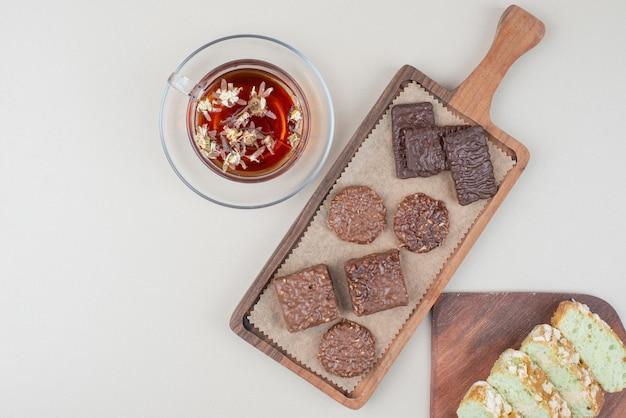 Biscotti al cioccolato, fette di torta al pistacchio e bicchiere di tè sulla superficie bianca