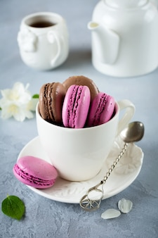 Chocolate and blackcurrant french macarons in ceramic cup of tea on light concrete.