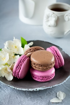 Chocolate and blackcurrant french macarons in ceramic plate on light concrete.