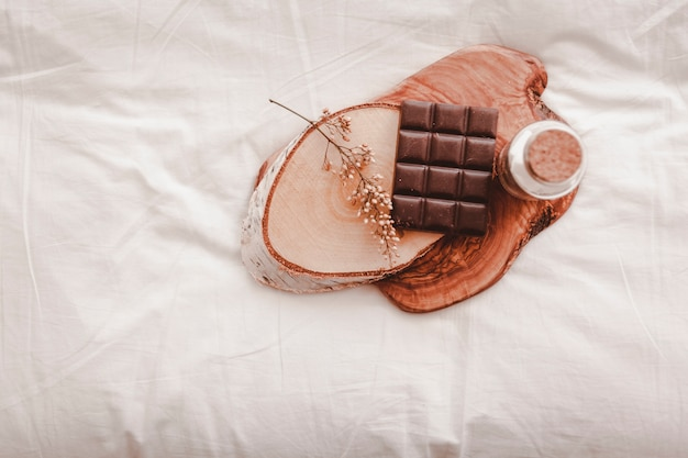 Chocolate and bottle on bed