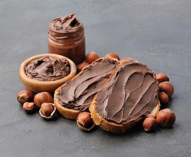 Шоколадный завтрак. хлеб с шоколадной пастой с крупным планом орехов фундука. тост с крупным планом орехового масла.