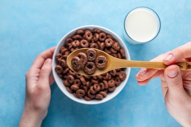 チョコレート、茶色、艶をかけられたリング、コップ1杯のミルクでドライでヘルシーな朝食をお楽しみください。上面図。シリアルスプーンとボウルに青いsurfceの手で