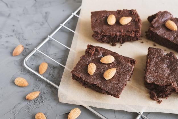 Шоколадный пирог, нарезанный небольшими квадратными кусочками, подается с миндалем