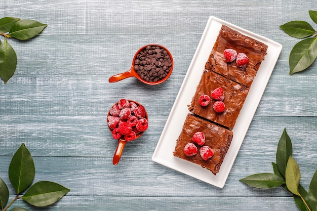 Chocolate brownie cake dessert slices with raspberries and spices,top view