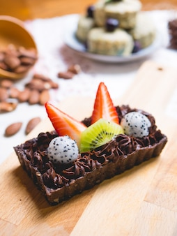 Chocolate brownie cake dessert with fruits on wooden board.